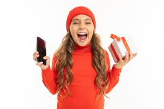Beautiful Caucasian Girl Holds A White Box With Gift In One Hand And A Smartphone In Other Hand, Smiles And Choises Stock Photography