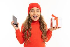 Beautiful Caucasian Girl Holds A White Box With Gift In One Hand And A Smartphone In Other Hand, Smiles And Choises Stock Images
