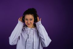 Beautiful caucasian girl listening to music in headphones in a sweatshirt on a purple background.  Stock Photography