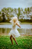 Wild dance by child. Beautiful caucasian girl with long blond hair in colorful dress dancing wild in the green grass by the river Royalty Free Stock Photo