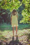 Little lovely girl in yellow dress under green tree. Beautiful caucasian girl with long blond hair in yellow dress standing  under the tree in summer time Royalty Free Stock Images