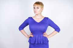 Beautiful caucasian girl with short hair and plus size body dressed in blue medium length dress in business style with peplum at t royalty free stock photography