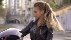 Beautiful caucasian girl sitting on a black motorcycle in the city. Young punk woman in fashion leather urban stock video