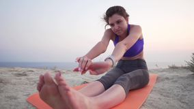 Beautiful caucasian girl in a top and with a smart watch suffers to do stretching while sitting on a sports mat on the stock video footage