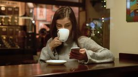 Beautiful Girl with Phone in Cafe. Beautiful caucasian girl using phone, she wearing gray sweater and having coffee in a nice, relaxing atmosphere stock video footage