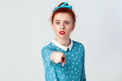 The beautiful caucasian girl, wearing blue dress, opening mouths widely, having surprised shocked looks, pointing finger at camera Royalty Free Stock Photography