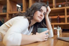 Beautiful Caucasian girl woman with long red hair sitting at a table with a mug of coffee or tea with a neutral expression royalty free stock image