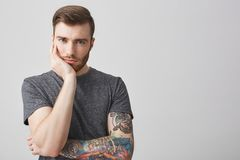 Beautiful caucasian mature man with ginger beard, trendy hairstyle and colored tattoo on arm holding head with hand Stock Photos