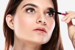 Beautiful caucasian model applying mascara. Close up portrait of beautiful caucasian model applying mascara royalty free stock images