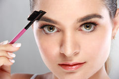 Beautiful caucasian model using an eyebrow brush. Close up portrait of beautiful caucasian model using an eyebrow brush royalty free stock photos