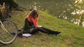 Beautiful caucasian smiling girl sits in the park with her bicycle, student writes in a notebook near a lake, warm stock video footage