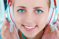Beautiful caucasian smiling woman wearing headphones and listening music. Royalty Free Stock Photography