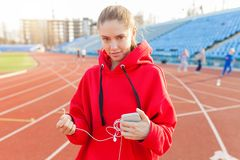 Beautiful caucasian sporty woman to fashionable red hoodie listens to music in headphones through smartphone royalty free stock photo