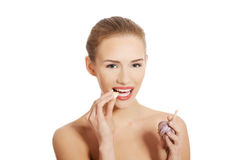 Beautiful caucasian topless woman with raw garlic in mouth. Stock Image