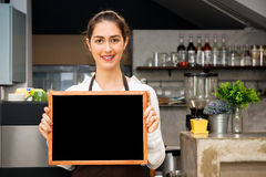 Beautiful Caucasian woman in barista apron holding empty blackboard sign inside coffee shop - ready to insert text Royalty Free Stock Photos
