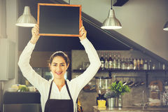 Beautiful Caucasian woman in barista apron holding empty blackboard sign inside coffee shop. Ready to insert text Royalty Free Stock Photography