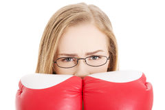 Beautiful caucasian woman behind boxing gloves. Royalty Free Stock Photo