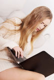 Beautiful caucasian woman in bright sweater is writing on laptop Royalty Free Stock Photos