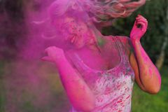 Beautiful caucasian woman in a cloud of pink dry paint, celebrating Holi festival. Beautiful caucasian girl in a cloud of pink dry paint, celebrating Holi stock photography