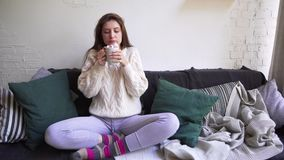 Beautiful caucasian woman is drinking coffee while sitting on a sofa with a plaid, blanket and pillows on a cloudy. Autumn day. 4k stock video