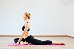 Beautiful caucasian woman exercising yoga indoors Royalty Free Stock Photos