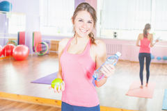 Beautiful caucasian woman after fitness exercise holding aple and water Stock Photos