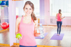 Beautiful caucasian woman after fitness exercise, holding apple and water Royalty Free Stock Photo