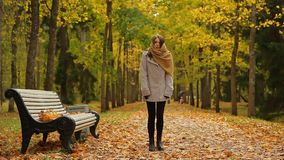 Beautiful caucasian woman in grey coat and knitted scarf in park at autumn. She waiting for someone, get cold and shaking stock video