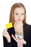 Beautiful caucasian woman is holding empty personal card and hou Royalty Free Stock Images