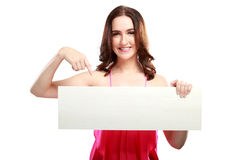 Beautiful caucasian woman holding and pointing at white board Royalty Free Stock Photos