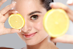 Beautiful caucasian woman holding and showing slices of lemon Stock Photography