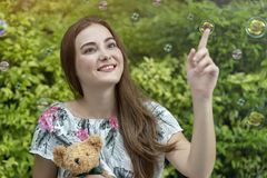 Beautiful caucasian woman hug teddy bear and playing soap bubbles outdoor at park. Relaxation and Freedom time royalty free stock photography