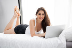 Beautiful Caucasian woman laying down on white bed using laptop and smile Royalty Free Stock Images