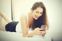 Beautiful Caucasian woman laying down on white bed using mobile phone and smile (Vintage tone) Stock Images