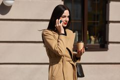 Beautiful Caucasian woman with long dark hair talking by phone with friend while standing on sunny street, brunette wearing beige stock photos