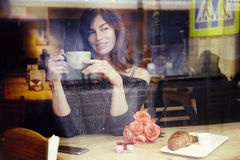 Beautiful caucasian woman with long hair near window in cafe, celebrating, present box and rose flowers. St. Valentine`s Day conce Royalty Free Stock Photos