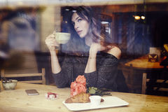 Beautiful caucasian woman with long hair near window in cafe. Romantic breakfast for a date or St. Valentine`s Day. Waiting someon Stock Images