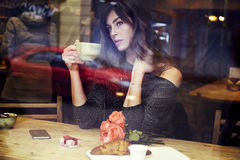 Beautiful caucasian woman with long hair near window in cafe. St. Valentine`s Day. Beautiful caucasian woman with long hair near window in cafe. Drinking coffee stock image
