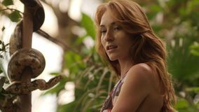Beautiful Caucasian woman with long wavy red hair wearing in floral print one-piece swimsuit. Ginger girl observe for. Snake in tropical garden. Freedom stock video footage