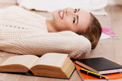 Beautiful caucasian woman lying on the floor with books. Stock Photography