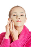 Beautiful caucasian woman in pink bathrobe with collagen mask. Stock Images