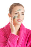 Beautiful caucasian woman in pink bathrobe is having facial mask Stock Photography
