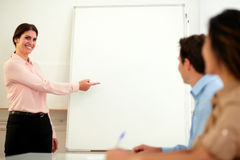Beautiful caucasian woman pointing at whiteboard Royalty Free Stock Photography