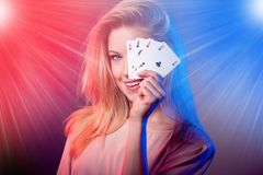 Beautiful caucasian woman with poker cards gambling in casino with light rays shining over her.  royalty free stock photos