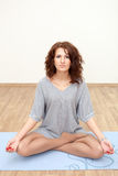 Beautiful Caucasian woman practicing yoga on floor Royalty Free Stock Photography
