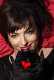Beautiful caucasian woman with red heart in hands Stock Images