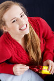 Beautiful caucasian woman in red sweater is unwrappind small pre Stock Photos