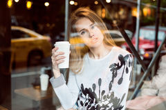 Beautiful caucasian woman sitting in city coffee shop near the window, drinking coffee from paper cup and looking at the camera Stock Photography