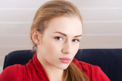 Beautiful caucasian woman sitting ona couch and wearing red pull Royalty Free Stock Photo