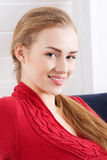 Beautiful caucasian woman sitting ona couch and wearing red pull Royalty Free Stock Photos